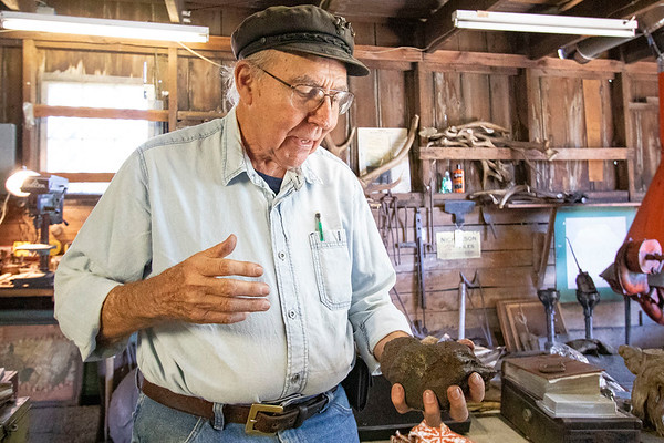 Blacksmith James Rubley showcases a meteorite Wednesday at his shop in Shipshewana.