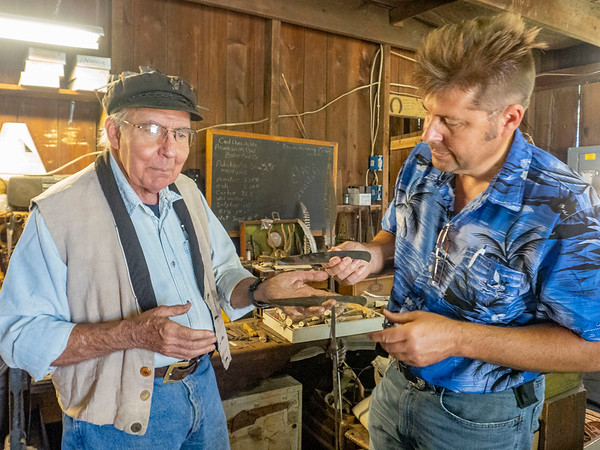 Blacksmith James Rubley, left, and his student Mark Yoder  showcase knives they are making Wednesday at his shop in Shipshewana.