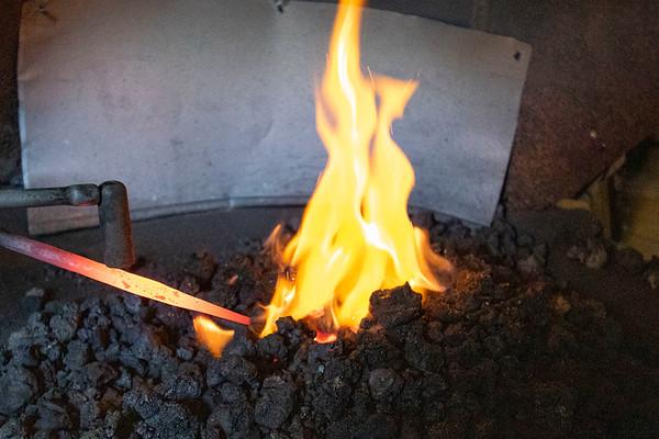 Blacksmith student Quinn Klopfensten inserts an iron rod into blacksmithing forge Wednesday at his shop in Shipshewana.