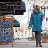 """Katherine Miller, of Goshen, looks into  a store front with a """"For your safety and others masks are required"""" sign in the 100 block of South Main Street on a brisk Tuesday afternoon in Goshen. Those who oppose the county's mask ordinance plan to rally in Goshen Friday."""