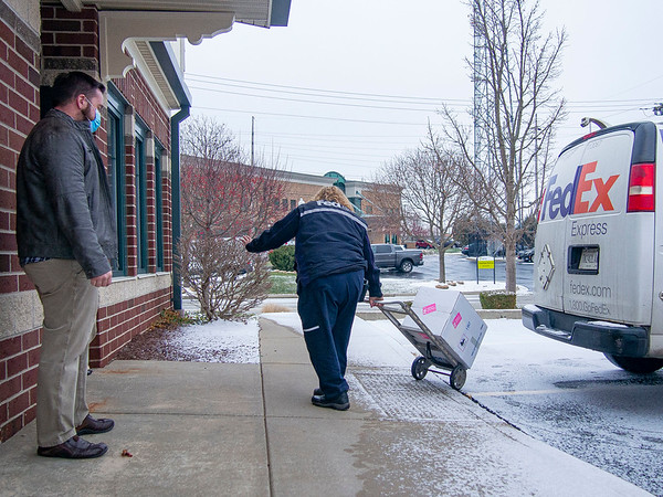 Goshen Health Director for Goshen Physicians Darrin Miller, left, observes a FedEx  driver delivery the first shipment of the Pfizer vaccine to Goshen Physicians Family Medicine Thursday morning at 400 W. Lincoln Ave. in Goshen. Goshen Health staff will begin to received the vaccinations Friday morning.