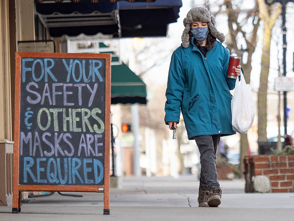 """Katherine Miller, of Goshen, walks along the sidewalk past a """"For your safety and others masks are required"""" sign in the 100 block of South Main Street on a brisk Tuesday afternoon in Goshen."""