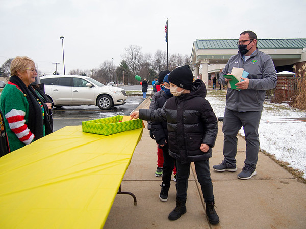 Daniel Panchelyuga, right,  drops a thank you letter for Cheryl Yoder, and her staff during the parade Thursday afternoon at Jefferson Elementary. The parade was to honor fighters, police, nurses, Middlebury Community Schools administration, Jefferson Community Church, and bus drivers. Over 1,000 items were donated to the Jefferson Food Pantry.