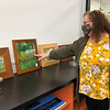 Diane Overmyer, a Plein Aire artist, shows the different flowers in Heather Telschow's garden that she painted. Several of Overmyer's paintings are fir sale at the Nappanee Art Center.