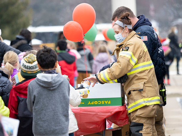 A Jefferson Township figherfighter receives a item from a student to be donated to the Jefferson Food Pantry during the parade Thursday afternoon at Jefferson Elementary. The parade was to honor fighters, police, nurses, Middlebury Community Schools administration, Jefferson Community Church, and bus drivers. Over 1,000 items were donated to the Jefferson Food Pantry.