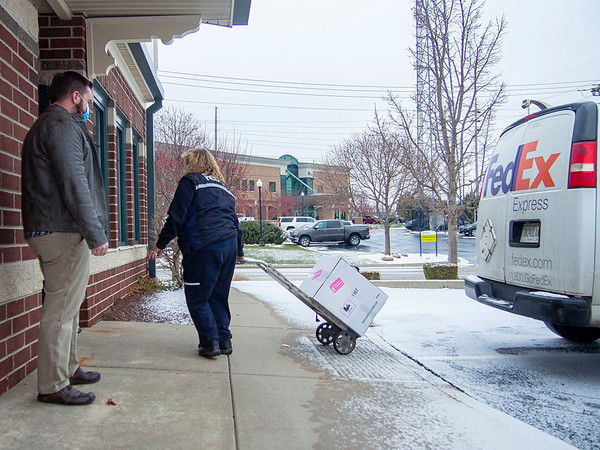 Goshen Health Director For Goshen Physicians Darrin Miller, left, observes a FedEx delivery driver of the first shipment of the Pfizer vaccine to Goshen Physicians Family Medicine Thursday morning at 400 W. Lincoln Ave. in Goshen.