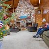Phil Wogoman, left, and Natalie Kochanowski speak during an interview at their home Thursday in Millersburg. Phil built the fire place in background out of rock from Arizona and is 30 feet tall. Natalie decorated their Christmas tree in a red, white, and blue tree to represent America.