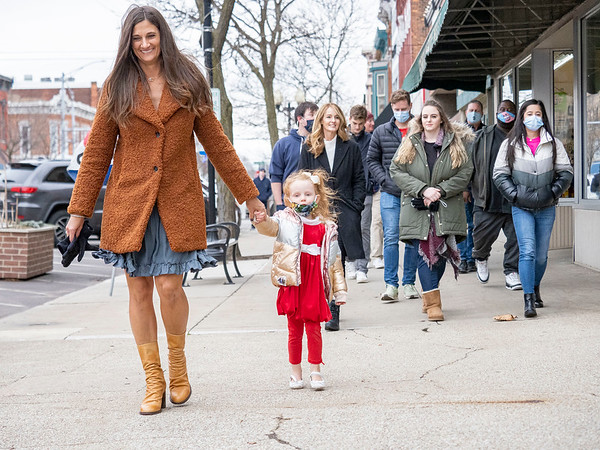 Lisa Graber, left, holds her great niece Elsie Blankinship, 3, walk along the sidewalk of South Main Street Wednesday afternoon with their family in Goshen. The family was walking back from The Window after making a donation. The family rented The Blank Space to host their Christmas gathering.