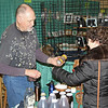 John Kline   The Goshen News<br /> Jim Curlee, a beekeeper and owner of Heather Valley Honey out of Lakeville, left, offers Annette Spitaels, of Nappanee, a sample of his honey during the annual Elkhart County Garden Expo at the Northern Indiana Event Center in Elkhart Saturday morning.