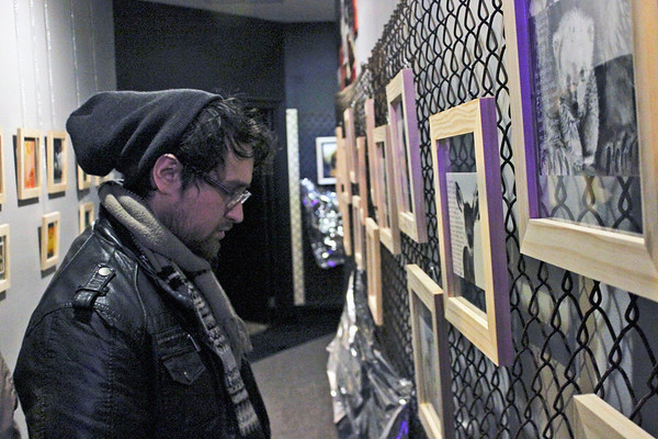Gabe Miller | The Goshen News<br /> Angel Reyes, who grew up in Goshen, looks at Amanda's paintings.