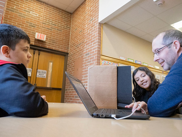 """Chandler Elementary fifth-grader co-producer Alec Nesbitt, 11, of Goshen, left, Andrew Kauffman, New Tech Instructional Coach, right, demonstrate to  Chandler Elementary fifth-grader Nadia Rodriguez, 10, of Goshen, how to playback and edit audio recordings for a podcast  after a Chandler Words by Design Podcast Wednesday. The podcasts are being produced to share the thoughts, stories, and ideas of some young creators. Our show is built around the ideas of students from one elementary school, looking to share our voices with the world. <br /> You can follow the podcast channel at this link: <a href=""""https://anchor.fm/andrew-kauffman7"""">https://anchor.fm/andrew-kauffman7</a>"""