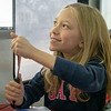 """Nadia Bechtel, 6, of Goshen, uses a thermometer to take the temperature of her hand to demonstrate how heat makes the temperature rise during the Ethos Innovation Center """"Science 2 Go"""" class on liquids, solids, and gasses Monday at Parkside Elementary."""