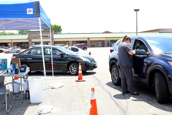 Indiana State Health Department site manager Katie Lemoreaux, right, and employee Victoria Konstantinidis check people in to be tested for COVID-19 Thursday afternoon at Trinity Square Shopping Center.