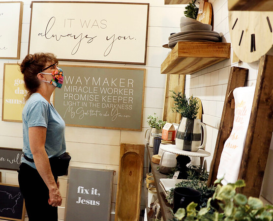 Pam Anecki of Port Huron, Michigan, looks at some of the signs at Joyfully Said in Middlebury Tuesday.