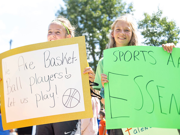 Lily Scholl, 11, left, and Allison Ambers, 12, both of Middlebury, hold up signs during the protest Friday at the Elkhart County Health Department in Elkhart.