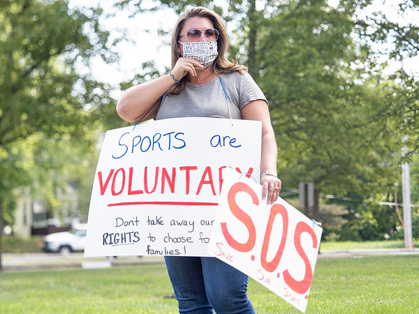 """Teri Wasquez holds a """"Sports are voluntary"""" sign during the protest Friday at the Elkhart County Health Department in Elkhart."""