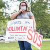 "Teri Wasquez holds a ""Sports are voluntary"" sign during the protest Friday at the Elkhart County Health Department in Elkhart."