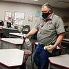 Goshen Schools custodial manager Dene Moore sprays desks and chairs in a classroom at Goshen High School. The desks will be moved farther apart before school starts for social distancing.