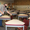 Dene Moore, custodial manager for Goshen Community Schools, sprays tables and chairs with a disinfectant at Goshen High School Tuesday.