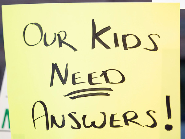 """A """"Our kids need answers"""" sign is held up during the protest Friday at the Elkhart County Health Department in Elkhart."""