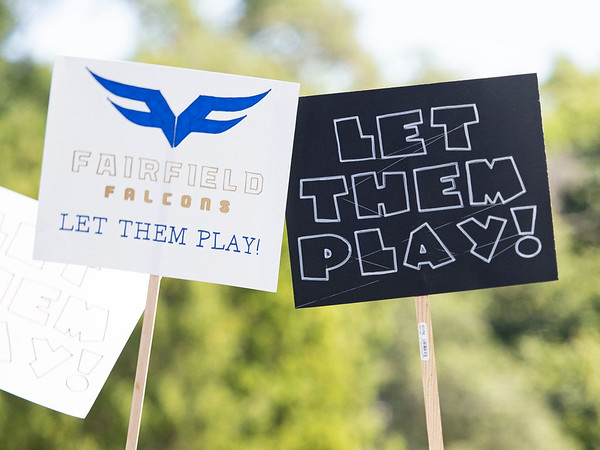 """""""Fairfield Falcons let them play"""" and a """"Let them play"""" signs appear during the protest Friday at the Elkhart County Health Department in Elkhart."""