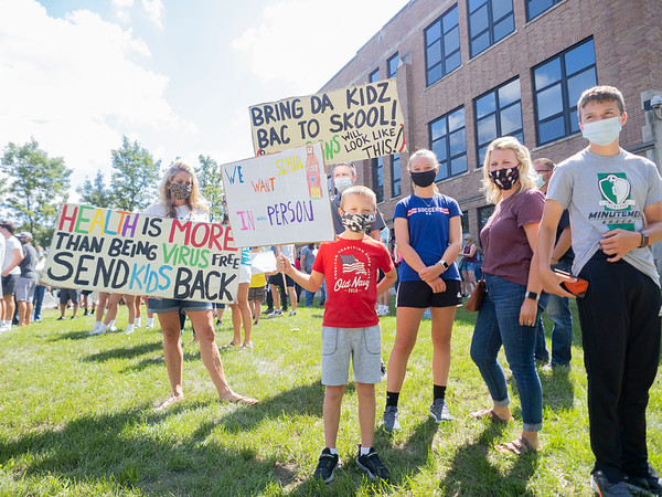 """Amy Brown, left, holds a """"Health is more than being virus free. Send kids back"""" sign and Camden Walter, 9, center front, of Elkhart, holds a """" We want schooling's person"""" sign during the protest Friday at the Elkhart County Health Department in Elkhart."""