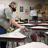Goshen Schools custodial manager Dene Moore sprays desks and chairs in a classroom Tuesday at Goshen High School. The desks will be moved farther apart before school starts for social distancing.