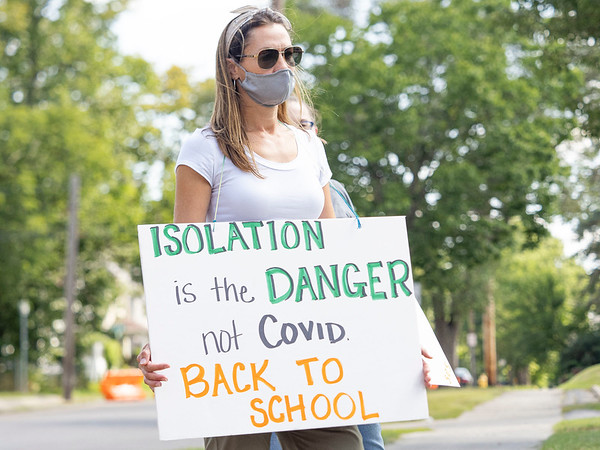 "Paula Gayler holds a ""Isolation is the danger not COVID back to school"" sign during the protest Friday at the Elkhart County Health Department in Elkhart."