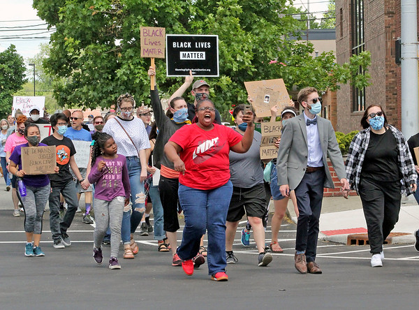 Roger Schneider | The Goshen News<br /> Protesters marched through downtown Goshen Saturday afternoon to protest the killing of George Floyd by Minneapolis, Minnesota police officers. Curbiee Coleman, in the red shirt, and Camden Chaffee, in the suit with bow tie, lead the march.