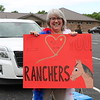 John Kline | The Goshen News<br /> Mary Brookins, a fourth grade teacher at Parkside Elementary School, holds up a sign for passing students during a special end-of-year drive-in celebration at Harvest Community Church Monday evening.
