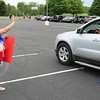 John Kline | The Goshen News<br /> Mary Brookins, a fourth grade teacher at Parkside Elementary School, waves to passing students during a special end-of-year drive-in celebration at Harvest Community Church Monday evening.
