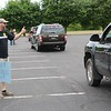 John Kline | The Goshen News<br /> John Moyer, a fourth grader teacher at Parkside Elementary School, give the thumbs up to passing students during a special end-of-year drive-in celebration at Harvest Community Church Monday evening.