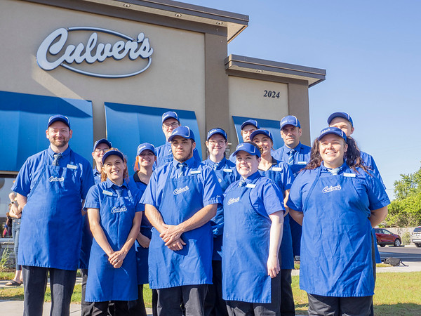 Culver's franchise co-owner Kevin Ray poses for a photo with his staff Monday morning during the ribbon cutting ceremony at the new Culver's on Elkhart Road in Goshen.