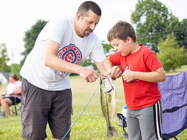 Silas Gingerich, 7, of Goshen, and his father retrieve the hook from the mouth of an 18-inch largemouth basss Saturday morning during the Fidler Pond's Fantastic Fishing Derby.