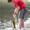 Silas Gingerich, 7, of Goshen, catches an 18-inch largemouth bass Saturday morning during the Fidler Pond's Fantastic Fishing Derby.