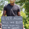 "Notre Dame Football player Jordan Genmark-Heath holds up a ""Never again will we relent, never again will we be silent. Power in unity."" sign at the at Irish Green on Notre Dame Campus Friday afternoon during Notre Dame's celebration of Juneteenth with peaceful prayer and walk."