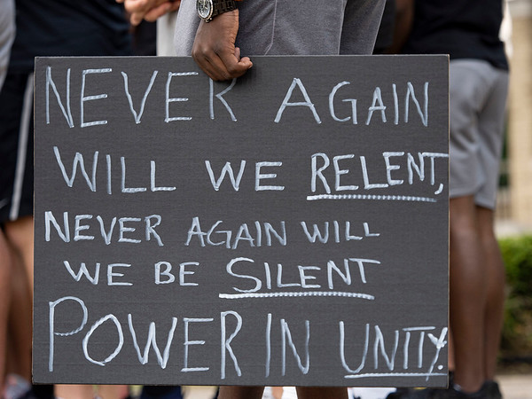 """Notre Dame Football player Jordan Genmark-Heath holds a """"Never again will we relent, never again will we be silent. Power in unity."""" sign at the at Irish Green on Notre Dame Campus Friday afternoon during Notre Dame's celebration of Juneteenth with peaceful prayer and walk."""