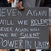 "Notre Dame Football player Jordan Genmark-Heath holds a ""Never again will we relent, never again will we be silent. Power in unity."" sign at the at Irish Green on Notre Dame Campus Friday afternoon during Notre Dame's celebration of Juneteenth with peaceful prayer and walk."