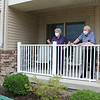 Eric Stoltzfus, left, listens as his parents, Paula and Eli, talk from the porch of Evergreen Place at Greencroft Goshen Friday afternoon.