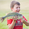 Silas Gingerich, 7, of Goshen, carries an 18-inch largemouth bass to be measured Saturday morning during the Fidler Pond's Fantastic Fishing Derby.