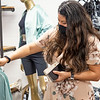 Goshen Centier Bank Manager Adriana Bontreger looks at an article of clothing after the ribbon cutting ceremony at Rose Lee Boutique on 114 E. Washington St., Goshen.