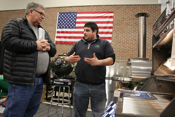 (from left) Tom Zablocki, Dowagiac, Michigan, listens to Carmin Liponoga of Kuert Outdoor Living as Liponoga describes specs of a pizza oven next to an outdoor grill at the company's exhibition space during the 2020 Elkhart Home & Outdoor Expo Saturday at Center Six One Five in Elkhart.