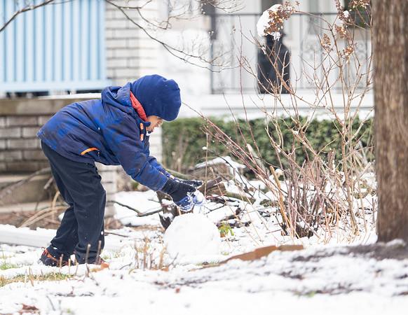 Trevor Black, 6, of Goshen, builds a snow man Monday morning along Fifth Street.