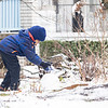 Trevor Black, 6, of Goshen, builds a snow man Monday morning along Fifth Street.