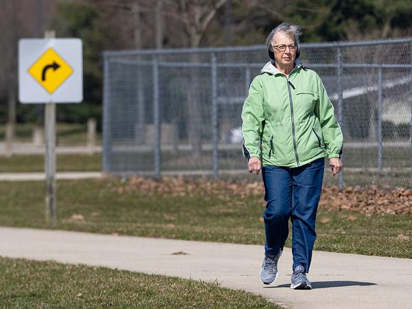 Rachel Wilcox, of Goshen, walks Wednesday afternoon along the Winona Railway Trail through Goshen College campus.
