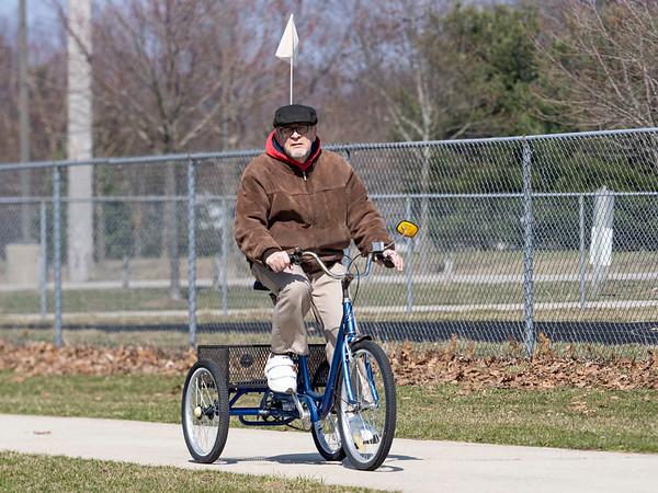 Robert Buzard, of Goshen, rides a trike Wednesday afternoon along the Winona Railway Trail through Goshen College campus.