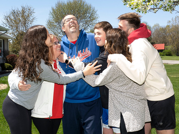 Tom Schermerhorn receives a group hug from his family at his home Wednesday afternoon in the 7000 block of West Highland Drive in Ligonier. Tom is a survivor of the COVID-19 virus and is on the road to recovery.