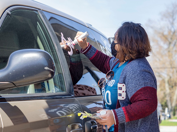 """May Day Rally participant writes on a vehicle supporting """"Indiana Joins Nationwide Car Caravans Demanding Dignity For Immigrant Workers"""" Friday afternoon in the parking lot of 2401 Middlebury Street, Elkhart."""