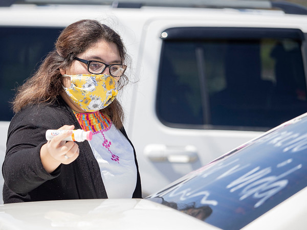 """Brenda Balcazar writes on a vehicle supporting """"Indiana Joins Nationwide Car Caravans Demanding Dignity For Immigrant Workers"""" Friday afternoon in the parking lot of 2401 Middlebury Street, Elkhart."""