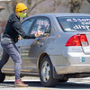 """Nicole Bauman, of Elkhart, writes on her vehicle supporting """"Indiana Joins Nationwide Car Caravans Demanding Dignity For Immigrant Workers"""" Friday afternoon in the parking lot of 2401 Middlebury Street, Elkhart."""